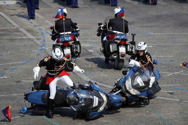 Two police motorcycles crash during a demonstration as part of the Bastille Day parade on the Champs Elysees avenue in Paris, France, Saturday, July 14, 2018. France's military is marching through Paris for Bastille Day celebrations and getting a budget boost from President Emmanuel Macron. (Photo by Francois Mori/AP Photo)