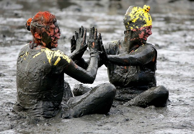Participants in the Mudflat Olympics' play  in the mud in Brunsbuettel, Germany, on July 28, 2013. At the Mudflat Olympics teams of different disciplines, such as  mud soccer, mud handball and mud sledding, compete against each other.  (Photo by Axel Heimken/DPA)