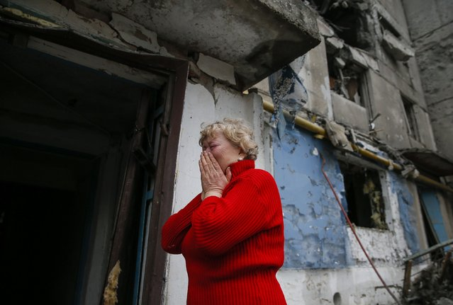 A woman reacts as she stands near a multi-storey block of flats damaged by shelling in Yenakieve town, northeast from Donetsk, February 2, 2015. (Photo by Maxim Shemetov/Reuters)