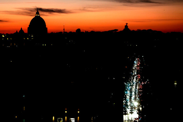 A photograph taken from the Pincino hill, at sunset on December 21, 2020 shows cars queuing in a traffic jam with Saint Peter's Dome in the background on the day of the winter solstice, in Rome. (Photo by Filippo Monteforte/AFP Photo)