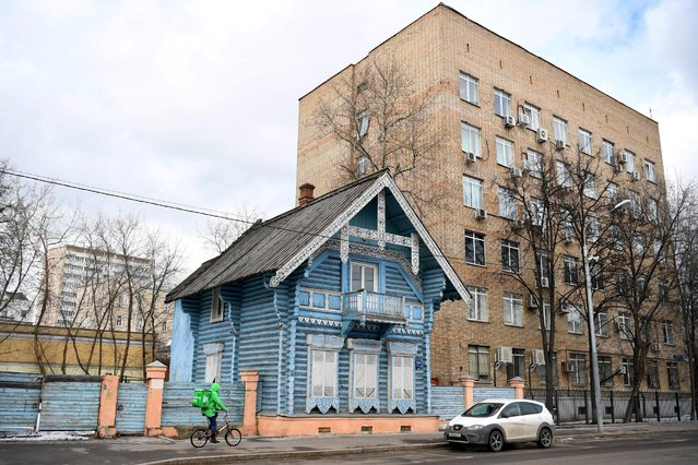 A food delivery courier cycles past a wooden house in Moscow on March 19, 2021. (Photo by Natalia Kolesnikova/AFP Photo)