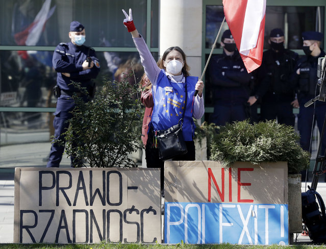 A woman wearing a vest inspired by the European Union flag and holding a Polish flag protests outside the Constitutional Tribunal in Warsaw, Poland, on Wednesday April 28, 2021. The constitutional court was to rule on Wednesday on whether Polish or European Union law has primacy in the country. It delayed its proceedings until May 13. Its ruling could affect the future relationship of the EU member nation with the rest of the bloc. (Photo by Czarek Sokolowski/AP Photo)
