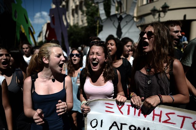 Students shout slogans during a demonstration in central Athens on September 18, 2013. As part of the controversial redeployment plan in the country reeling from six years of recession, civil servants have to accept new posts or spend eight months on reduced salaries as alternative posts are found, with the risk of losing their jobs altogether. (Photo by Aris Messinis/AFP Photo)