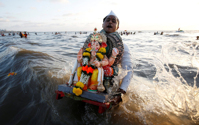 A devotee carries an idol of the Hindu god Ganesh, the deity of prosperity, to immerse into the Arabian Sea on the fifth day of Ganesh Chaturthi festival in Mumbai, India, September 17, 2018. (Photo by Francis Mascarenhas/Reuters)