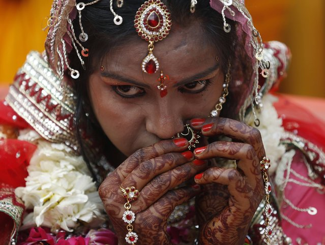 A bride gets ready during a mass wedding ceremony in the old quarters of Delhi February 20, 2015. (Photo by Ahmad Masood/Reuters)