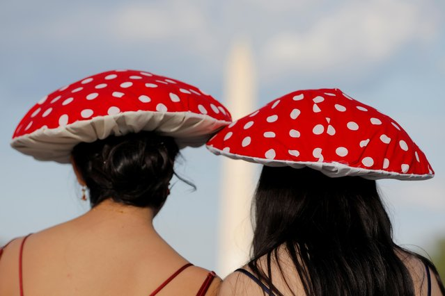 People wearing mushroom hats stand in front of the Washington Monument in Washington, D.C., U.S., May 14, 2021. (Photo by Andrew Kelly/Reuters)