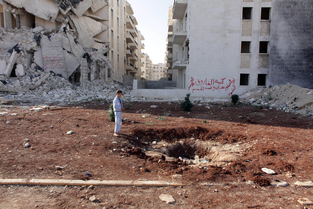 Essay Finalist – William Wintercross. A boy stares into a bomb crater amidst damage to his neighbourhood in Aleppo. (Photo by William Wintercross/The Daily Telegraph)