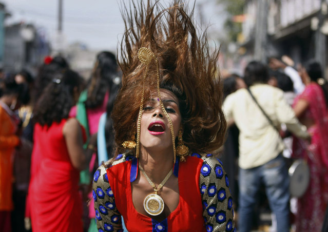 A eunuch dances during a rally to mark the congregation of thousands of eunuchs from different parts of India, in Jammu, India, Friday, March 13, 2015. The term eunuchs is used in India to describe transvestites, transsexuals and others who identify themselves as neither male nor female but as a member of a third gender. They traditionally survive by begging, dancing at weddings or blessing newborn babies and are frequently subjected to discrimination. (Photo by Channi Anand/AP Photo)