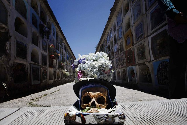 A decorated human skull sits in a box at the Cementerio General. (Photo by Juan Karita/Associated Press)