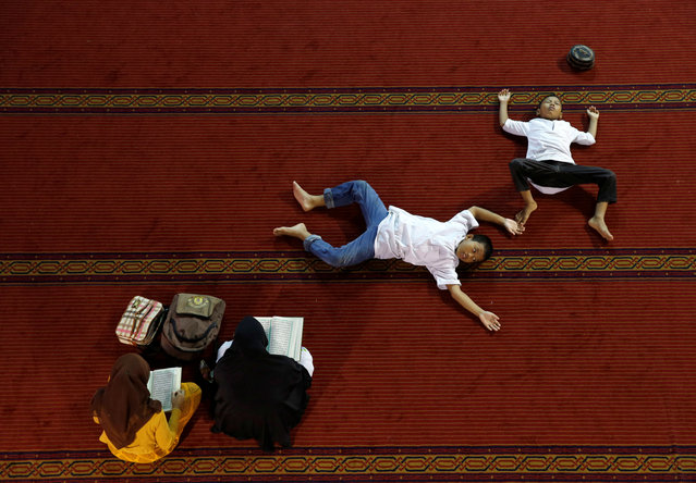 INDONESIA: Women read the Koran as boys rest inside Istiqlal mosque during the holy month of Ramadan in Jakarta, Indonesia June 9, 2016. (Photo by Reuters/Beawiharta)