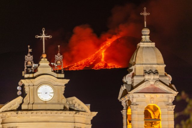 Lava erupts from a crater of Mt. Etna, Europe's largest active volcano, behind Santa Maria della Guardia church in Belpasso, near Catania, in southern Italian island of Sicily, early Friday, June 18, 2021. Since Feb. 16, 2021, Mt. Etna has begun a series of spectacular eruptive episodes. (Photo by Salvatore Allegra/AP Photo)