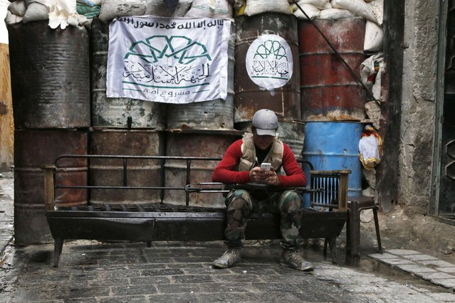 """A rebel fighter uses his mobile phone beside barriers at a frontline in Old Aleppo January 4, 2015. The text on the flag reads, """"There is no God but Allah, The Islamic Front, A nation project"""". (Photo by Hosam Katan/Reuters)"""