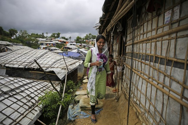 In this August 27, 2018, photo, Rahima Akter walks through Balukhali refugee camp in Bangladesh. Rahima is a 19-year-old refugee who dreams of becoming the most educated Rohingya woman in the world. She recently finished high school and hopes to study human rights in college. (Photo by Altaf Qadri/AP Photo)