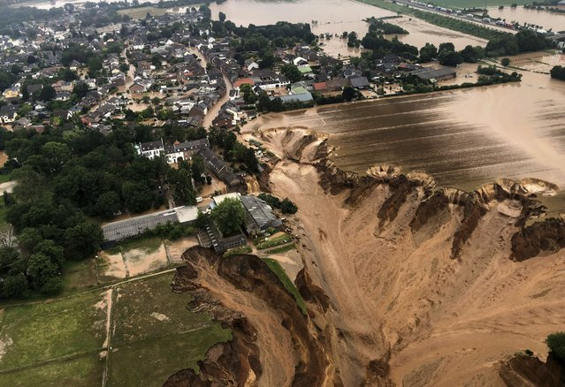 This image provided on Friday, July 16, 2021 by the Cologne district government shows the Blessem district of Erftstadt in Germany. Rescuers were rushing Friday to help people trapped in their homes in the town of Erftstadt, southwest of Cologne. Regional authorities said several people had died after their houses collapsed due to subsidence, and aerial pictures showed what appeared to be a massive sinkhole. (Photo by Rhein-Erft-Kreis via AP Photo)