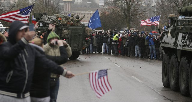 US army soldiers wave to their supporters as they arrive with their convoy in Prague, Czech Republic, Monday, March 30, 2015. (Photo by Petr David Josek/AP Photo)