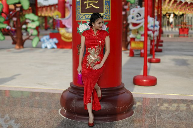 A woman poses for a picture taken by her friend (not in picture) in a temple decorated to celebrate Chinese New Year at Samut Prakan province outside Bangkok February 7, 2016. (Photo by Jorge Silva/Reuters)
