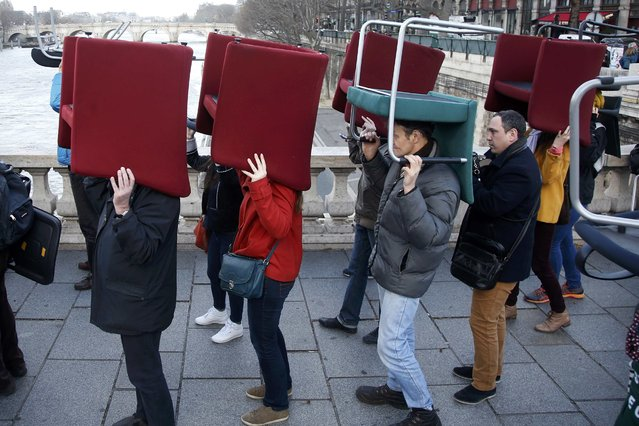 Demonstrators carry chairs that were stolen from bank offices in France to protest against a banking system and tax fraud, as they gather on a bridge near the courts in Paris, France, February 8, 2016. Former French budget minister Jerome Cahuzac, who resigned in 2013 after he admitted to have a Swiss bank account, stands trial on Monday for tax fraud. (Photo by Charles Platiau/Reuters)