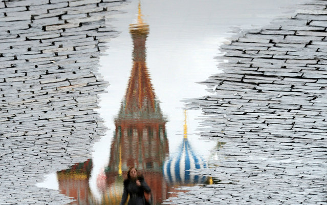 This photo, rotated 180 degrees, shows a woman being reflected in a puddle as she walks past landmark St.Basil's Cathedral  at the Red Square in Moscow, on November 29, 2013. (Photo by Kirill Kudryavtsev/AFP Photo)