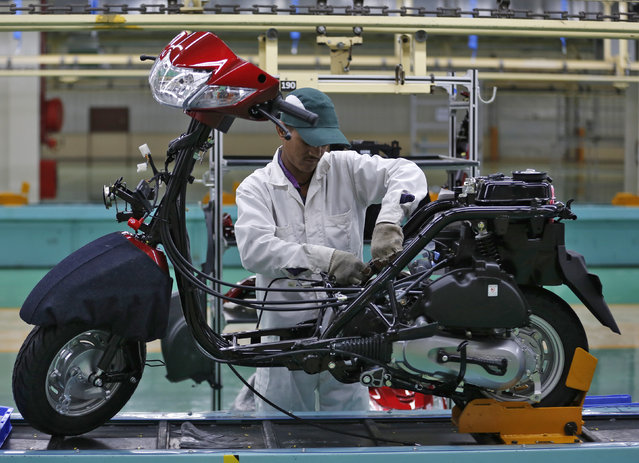 An employee works on an assembly line of Honda Motorcycle & Scooter India during a media tour to the newly inaugurated plant at Vithalapur town in the western state of Gujarat, India, February 17, 2016. (Photo by Amit Dave/Reuters)
