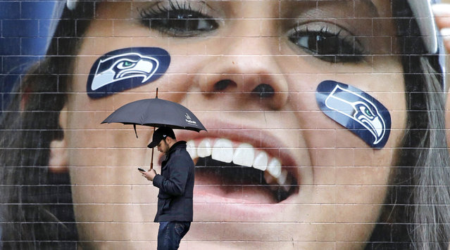 A pedestrian walks past a large photo of a cheering Seattle Seahawks' fan outside the team's NFL football stadium Tuesday, February 3, 2015, in Seattle. The grief, anger and bewilderment felt by many Seahawks fans after the team's loss to the New England Patriots in the Super Bowl shows little sign of abating, even days later. (Photo by Elaine Thompson/AP Photo)