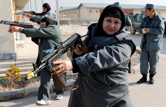 Female Afghan National Police (ANP) officers aim their weapons during a drill at a training centre near the German Bundeswehr army camp Marmal in Mazar-e-Sharif, northern Afghanistan on December 11, 2012. (Photo by Fabrizio Bensch/Reuters/File Photo)