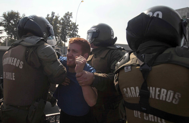 A protester is detained by police during a demonstration in Santiago, Chile, Thursday, April 16, 2015. (Photo by Luis Hidalgo/AP Photo)
