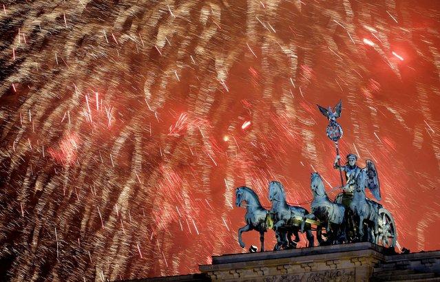 Fireworks light the sky above the Quadriga at the Brandenburg Gate in Berlin, Germany. (Photo by Michael Sohn/Associated Press)