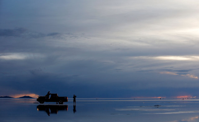 A car is pictured as the sun sets over the Salar de Uyuni or Uyuni Salt Flat during Day 7 of the 2014 Dakar Rally on January 11, 2014 in Uyuni, Bolivia. (Photo by Dean Mouhtaropoulos/Getty Images)