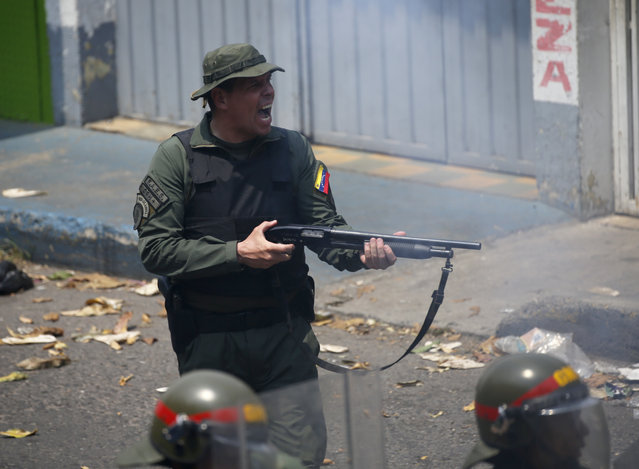 An officer of the Bolivarian National Guard fires his shotgun during clashes in Urena, Venezuela, near the border with Colombia, Saturday, February 23, 2019. Venezuela's National Guard fired tear gas on residents clearing a barricaded border bridge between Venezuela and Colombia on Saturday, heightening tensions over blocked humanitarian aid that opposition leader Juan Guaido has vowed to bring into the country over objections from President Nicolas Maduro. (Photo by Fernando Llano/AP Photo)