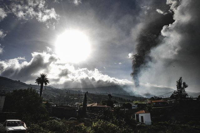 Smoke billows from a volcano near Los Llanos de Ariadne on the island of La Palma in the Canaries, Spain, Tuesday September 21, 2021. Several small earthquakes have shaken the Spanish island of La Palma off northwest Africa, keeping nerves on edge as rivers of lava continue to flow toward the sea after Sunday's volcanic eruption with the lava gradually closing in on the more densely populated coastline. (Photo by k*ke Rincon/Europa Press via AP Photo)