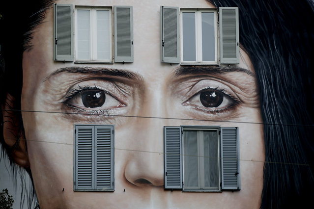 An art wall painting representing performance artist Marina Abramovic by Italian artist Maurizio Cattellan to publicize his upcoming exhibition The Artist is Present, in Shanghai, China, is displayed on a facade of a building, in Milan, Italy, Wednesday, September 19, 2018. (Photo by Luca Bruno/AP Photo)