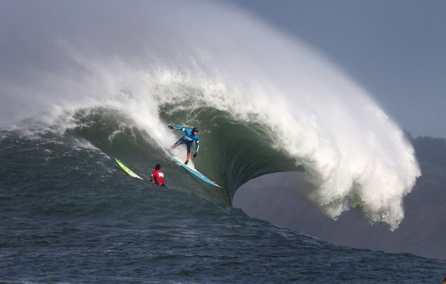 Peter Mel takes off on a wave as fellow competitor Colin Dwyer looks on in the second heat of Round 1 during the Maverick's Big Wave Invitational surfing contest at Half Moon Bay, Calif., on Friday, January 24, 2014. (Photo by Patrick Tehan/Bay Area News Group/MCT)