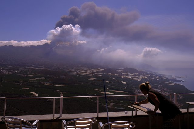 A worker cleans the ash from the tables of a restaurant as lava flows from a volcano on the Canary island of La Palma, Spain on Monday October 4, 2021. More earthquakes are rattling the Spanish island of La Palma, as the lava flow from an erupting volcano surged after part of the crater collapsed. Officials say they don't expect to evacuate any more people from the area, because the fiery molten rock was following the same route to the sea as earlier flows. (Photo by Daniel Roca/AP Photo)