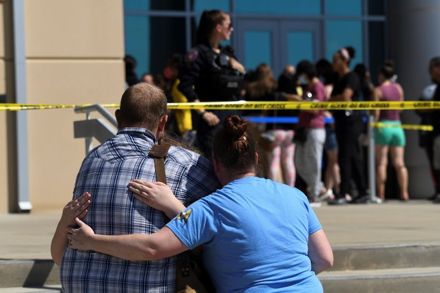 Timberview Chemistry teacher Blake Wade embraces his wife Stephanie and daughter Keeley as they are reunited at Mansfield Center for Performing Arts after a shooting at Mansfield Timberview High School in Arlington, Texas, U.S. October 6, 2021. (Photo by Jeremy Lock/Reuters)