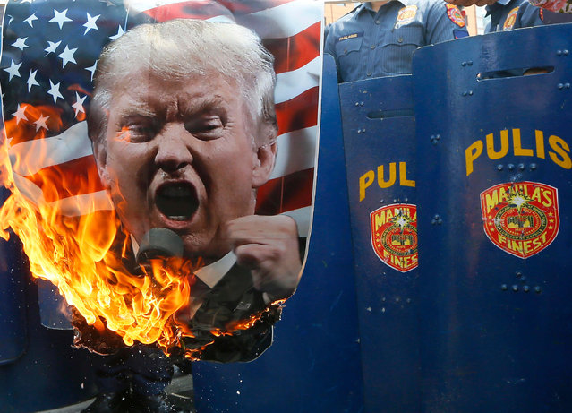 Protesters burn a portrait of U.S. President Donald Trump in front of riot police during a rally in front of the U.S. Embassy Saturday, February 4, 2017 in Manila, Philippines. The protesters scored Trump on his anti-immigration stance. (Photo by Bullit Marquez/AP Photo)