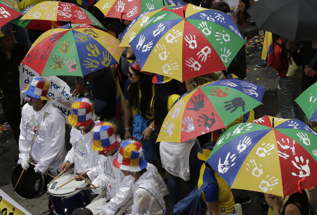 Workers march holding umbrellas marked with palm prints, symbolizing clean hands, free of corruption, during a May Day parade in a show of support for Ecuador's President Rafael Correa, in Quito, Ecuador, Friday, May 1, 2015. (Photo by Dolores Ochoa/AP Photo)