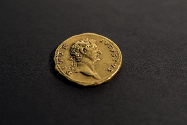 """An extremely rare 24-karat gold coin showing the Roman Emperor Augustus and dated to almost 2,000 years ago is displayed in the Israeli Antiquities Authority offices in the Israel Museum in Jerusalem, 14 March 2016. The coin was discovered by a hiker in the northern Galilee area of Israel some two weeks ago and turned over to the Israel Antiquities Authority. The coin was issued by the Emperor Trajan and reads """"Deified Augustus"""". (Photo by Jim Hollander/EPA)"""