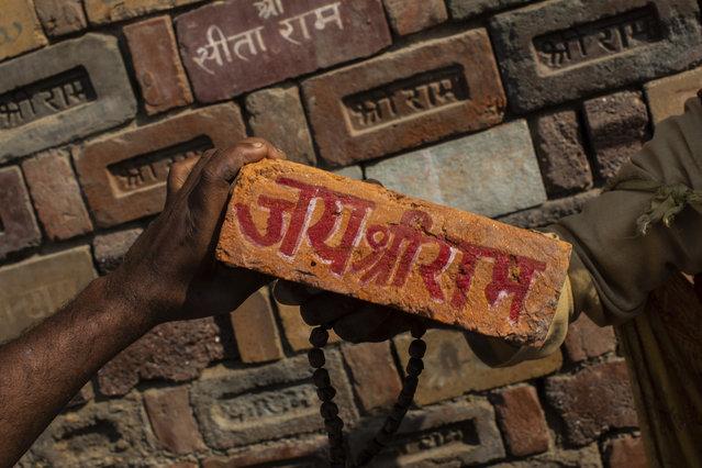 "In this Sunday, November 25, 2018 photo, a man holds a brick reading ""Jai Shree Ram"" (Victory to Lord Ram) as bricks of the old Babri Mosque are piled up in Ayodhya Uttar Pradesh, India. (Photo by Bernat Armangue/AP Photo)"