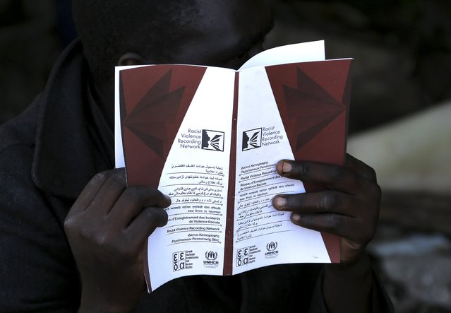 A Sudanese immigrant reads a pamphlet distributed by the UNHCR on racism in the western Greek town of Patras May 4, 2015. (Photo by Yannis Behrakis/Reuters)