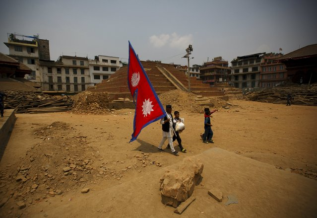 A man holding a Nepalese flag walks along the collapsed temple at Bashantapur Durbar Square, a UNESCO world heritage site, after the April 25 earthquake at Kathmandu May 7, 2015. (Photo by Navesh Chitrakar/Reuters)