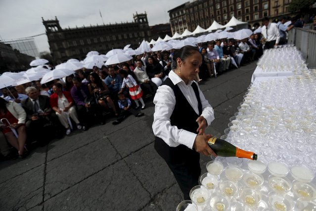 A waitress pours out champagne during a mass wedding ceremony in which 2,016 couples participated, at Zocalo square in Mexico City, Mexico, March 19, 2016. (Photo by Edgard Garrido/Reuters)