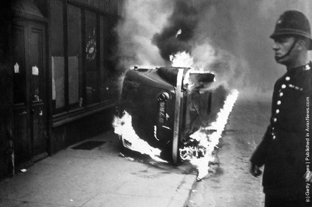 A policeman stands by a burning car, 1936