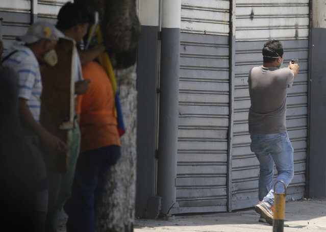 An opponent to Venezuela's President Nicolas Maduro aims a gun at security forces loyal to Maduro during protests in Caracas, Venezuela, Tuesday, April 30, 2019. (Photo by Ariana Cubillos/AP Photo)