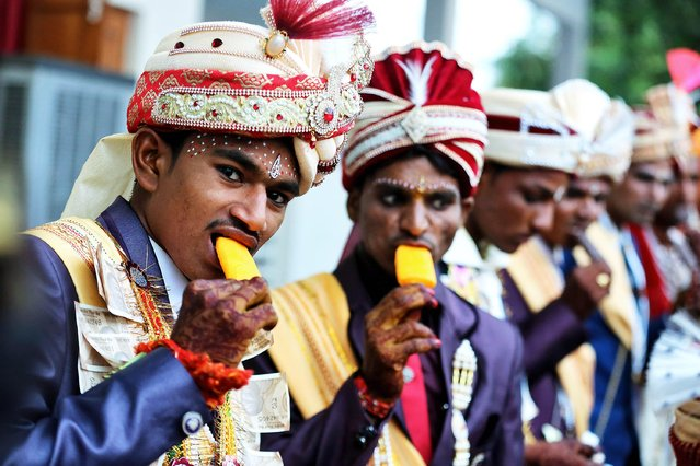 "Bridegrooms of the Pal community eat ice lollies during a mass marriage ceremony on the occasion of the ""Akshay Tritiya"" festival in Bhopal, India, 07 May 2019. Akshay Tritiya is considered one of the most auspicious days of the Hindu calendar. It is believed, any meaningful activity that started on this day would be fruitful. More than 52 couples of the community tied the nuptial knot during the mass marriage ceremony. (Photo by Sanjeev Gupta/EPA/EFE)"