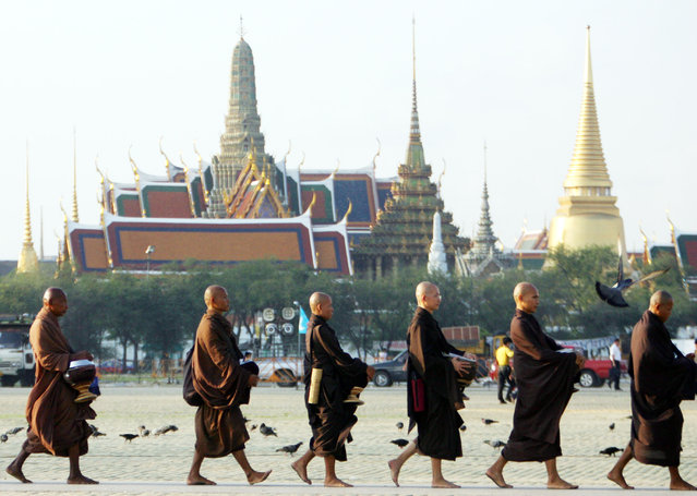 In this February 2006, file photo, Thai monks walk in front of Grand Palace at Sanam Luang in Bangkok, Thailand. The official coronation of Thailand's King Maha Vajiralongkorn, who is also known as Rama X, involves months of rituals that will culminate in three days of elaborate pageantry, May . 4-6, 2019, including a parade and an appearance by the king on a balcony of the Grand Palace. The final event will be a royal barge procession in October, 2019. (Photo by Wasan Wanichakorn/AP Photo/File)