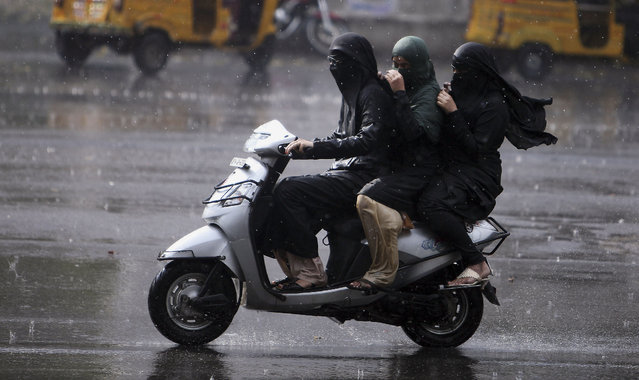Indian women covered in burqa, or veil, travel on a two wheeler in the rain in Hydrabad, India, Sunday, March 2, 2014. The city received heavy rainfall, leading to waterlogging in the streets, according to local reports. (Photo by Mahesh Kumar A./AP Photo)