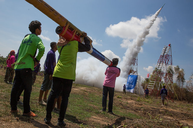 Thai teammates wait for a rocket to take off before mounting their rocket at the launching area at the Bun Bang Fai Rocket Festival on May 10, 2015 in Yasothon, Thailand. (Photo by Taylor Weidman/Getty Images)