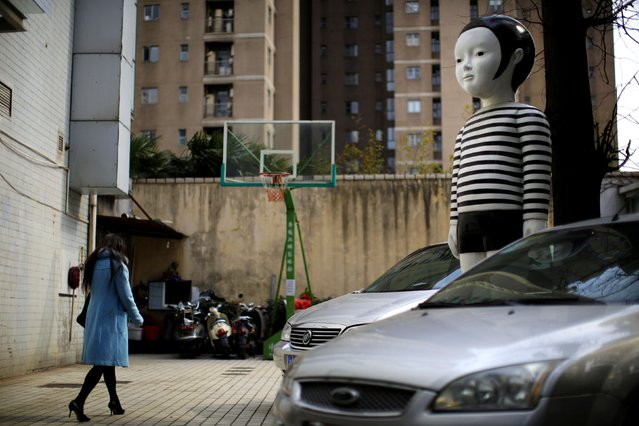 A giant doll boy is seen at an apartment parking area in downtown Shanghai March 7, 2014. (Photo by Carlos Barria/Reuters)