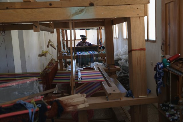 Indigenous Mayan weaver Delfina Perez, who's husband has worked in the U.S. as an immigrant for 20 years, works on a foot loom at the Grupo Cajola weaving cooperative on February 11, 2017 in Cajola, Guatemala. Women are especially effected by emigration from Guatemala, where some 70 percent of the men have left to work as undocumented immigrants in the United States, many of them leaving behind wives and children who only know their fathers online, if at all. (Photo by John Moore/Getty Images)