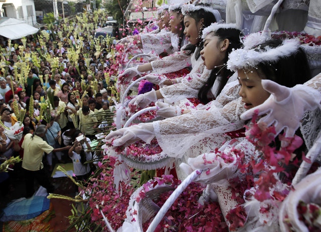 Filipino children shower flower petals onto Catholic devotees holding decorative palm fronds during a procession to mark Palm Sunday at a street in Las Pinas City, south of Manila, Philippines, 14 April 2019. Palm Sunday for Roman Catholic devotees symbolically marks the biblical account of the entry of Jesus Christ into Jerusalem, signaling the start of the Holy Week. (Photo by Francis R. Malasig/EPA/EFE)